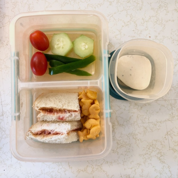 Toddler lunch of peanut butter and jelly, Goldfish, and vegetables with dip