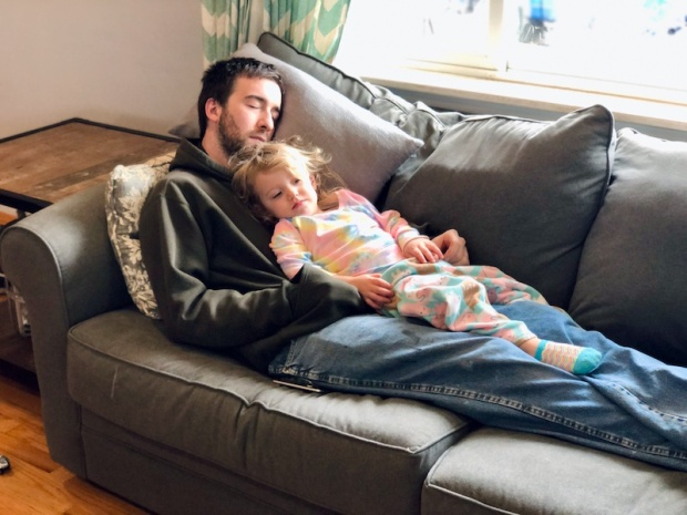 Dad and toddler snuggling on couch together
