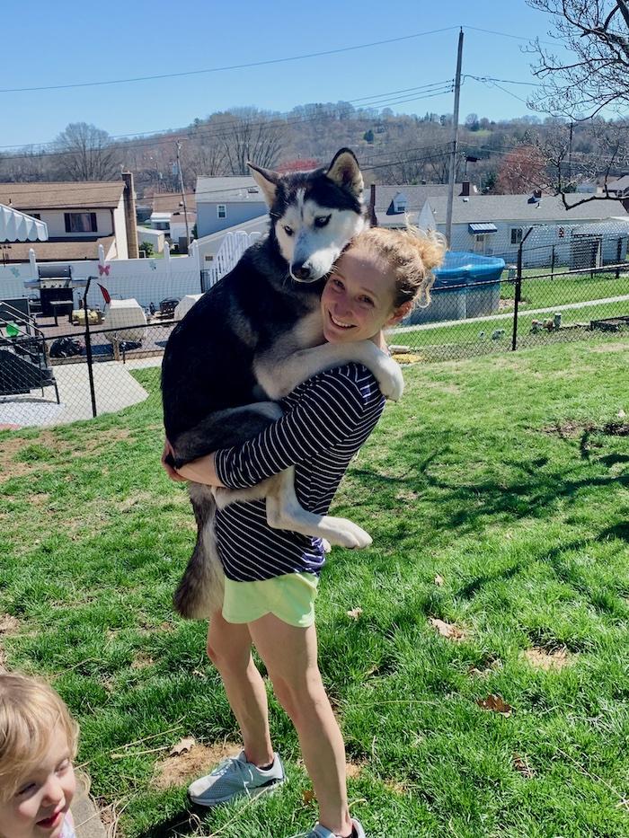 Girl holding husky like a child
