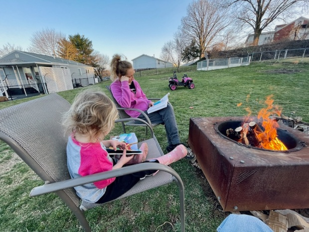 Mom and daughter reading by a bonfire
