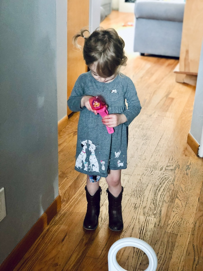 Toddler wearing 101 Dalmatians dress and cowboy boots while looking at Skye Paw Patrol watch.