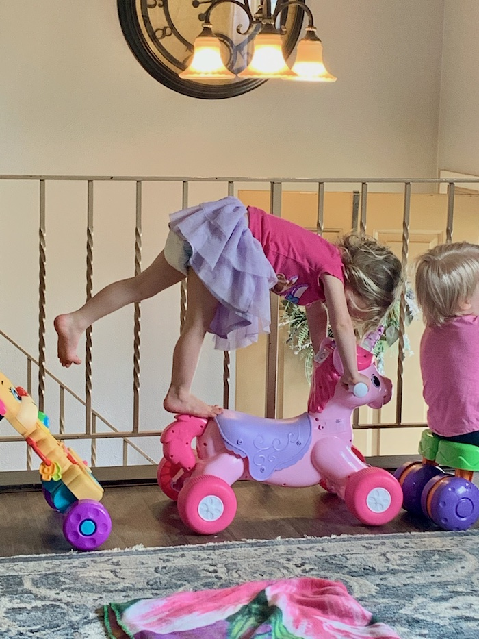 Toddler girl balancing on one foot on toy.
