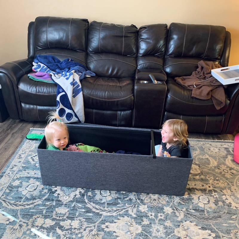 Toddlers sitting inside of ottoman