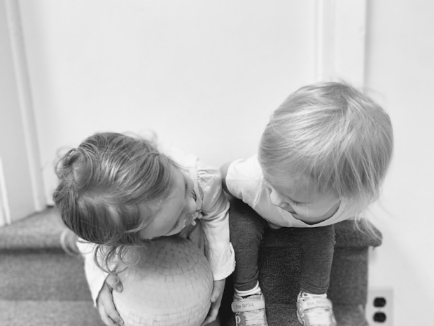 Black and white photo of toddler girls looking at each other