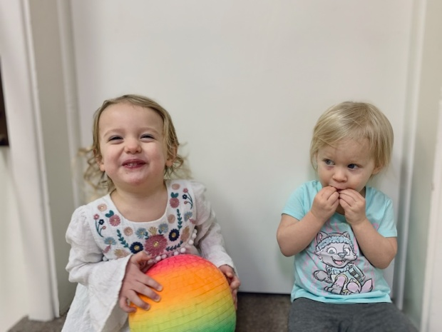 Toddler girls sitting together with ball