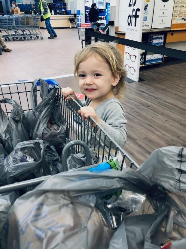 Toddler standing on cart at Walmart