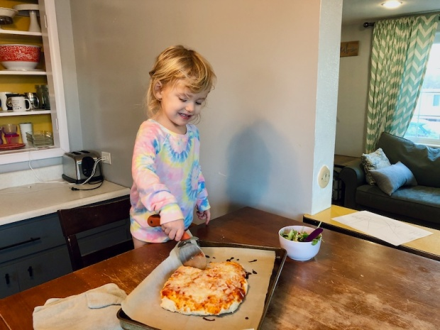 Toddler cutting homemade pizza