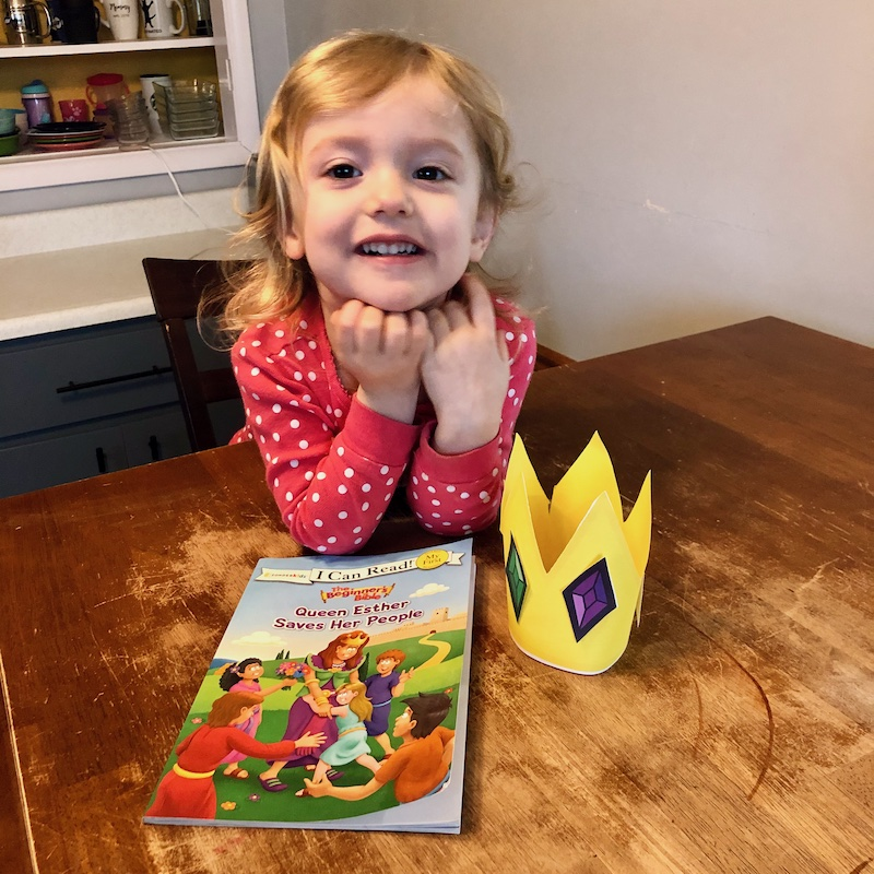 Toddler reading Queen Esther Saves Her People and doing a crown craft