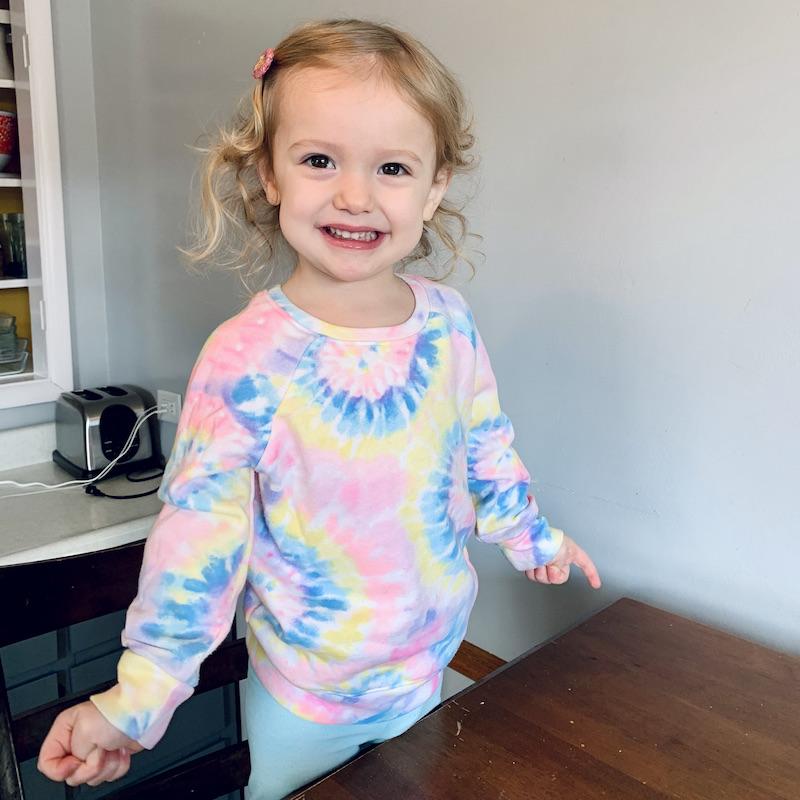 Toddler girl wearing multi-color tie dye sweatshirt