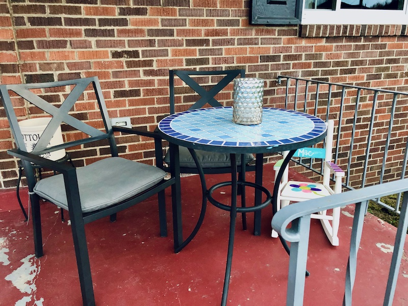 Blue bistro table with black chairs and toddler rocking chair