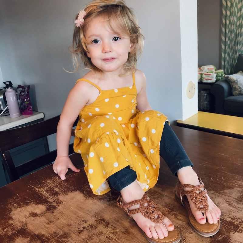 Toddler girl wearing sandals and yellow polka dot dress from Old Navy