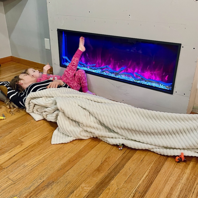 Mom and daughter laying by modern fireplace.