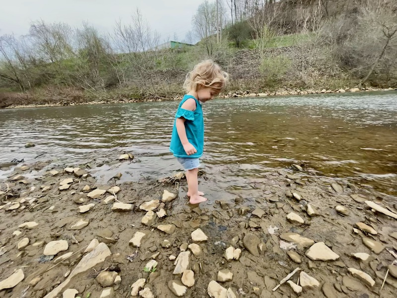 Toddler standing in mud in creek in Pittsburgh