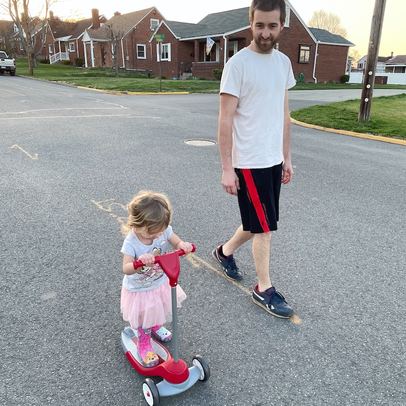 Toddler girl riding scooter with a skirt on