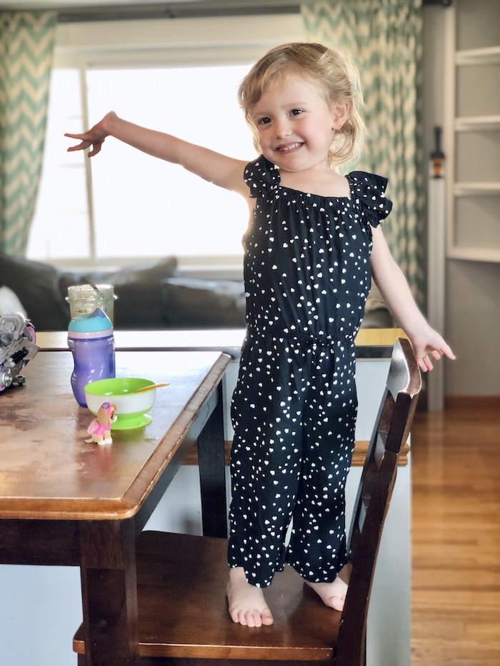 Toddler girl wearing black jumpsuit with white hearts