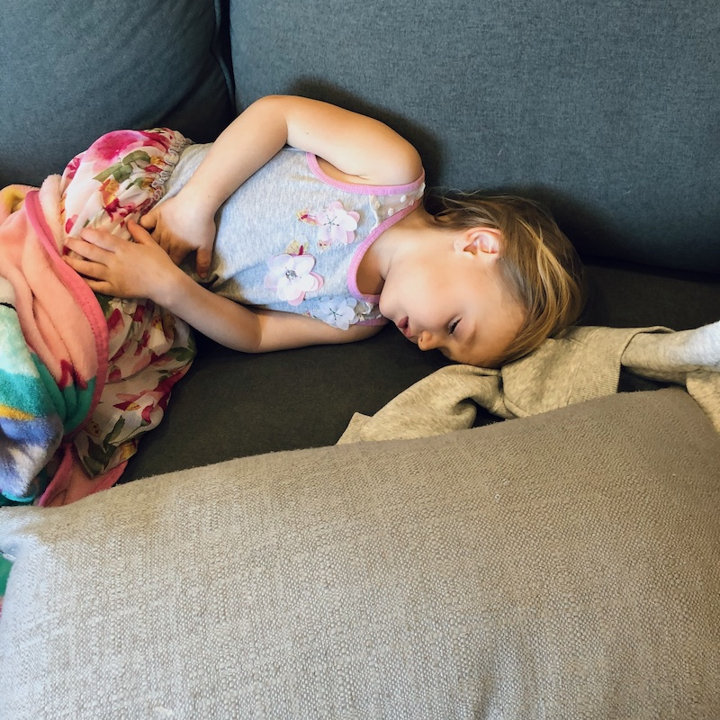 Toddler laying on couch sick with stomach bug.
