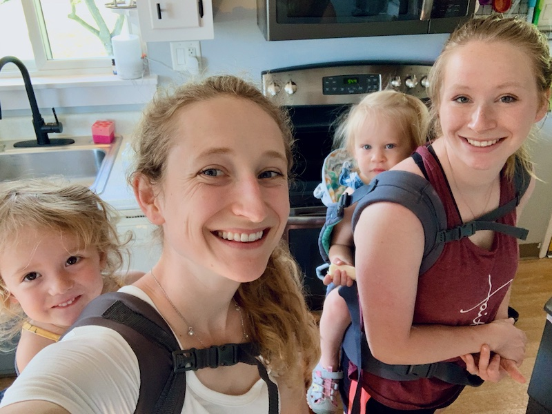 Sisters with their babies in carriers on their backs