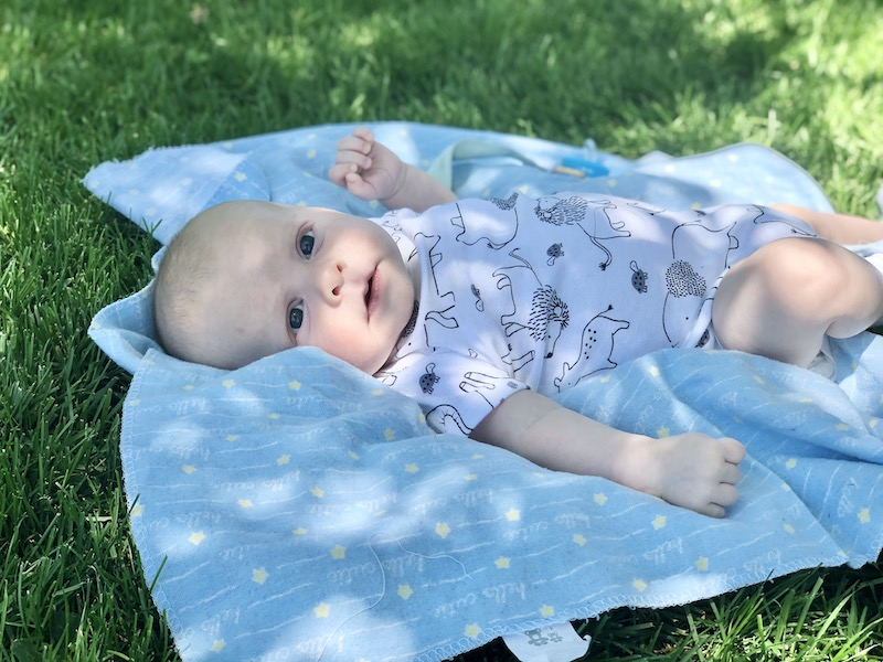 Two month old baby boy laying on a blanket in grass