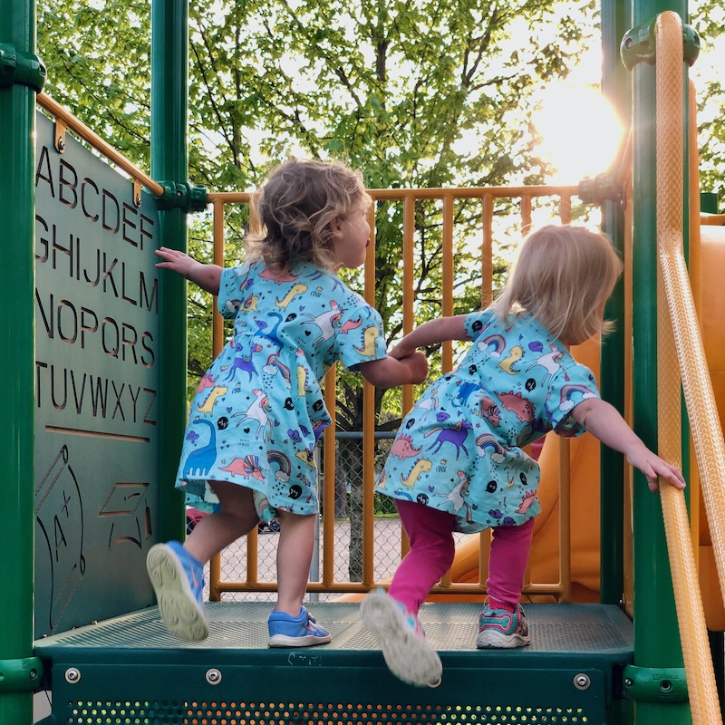 Toddler girls wearing matching dresses and holding hands at playground