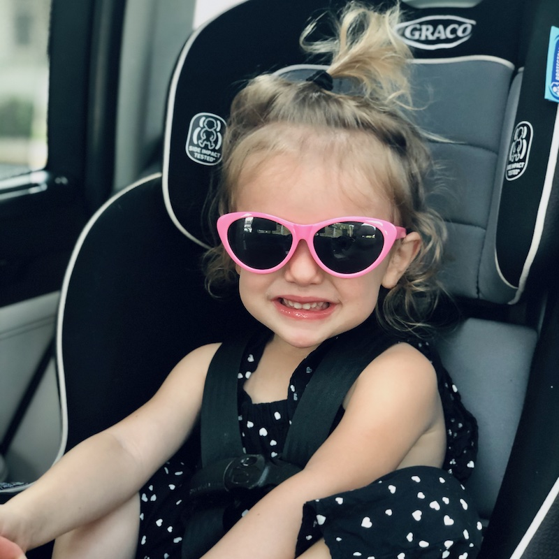 Toddler girl sitting in carseat wearing pink sunglasses and smiling
