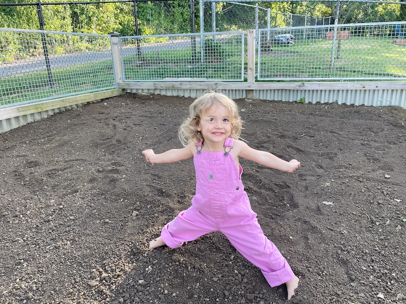 Toddler playing in dirt in Carhartt overalls