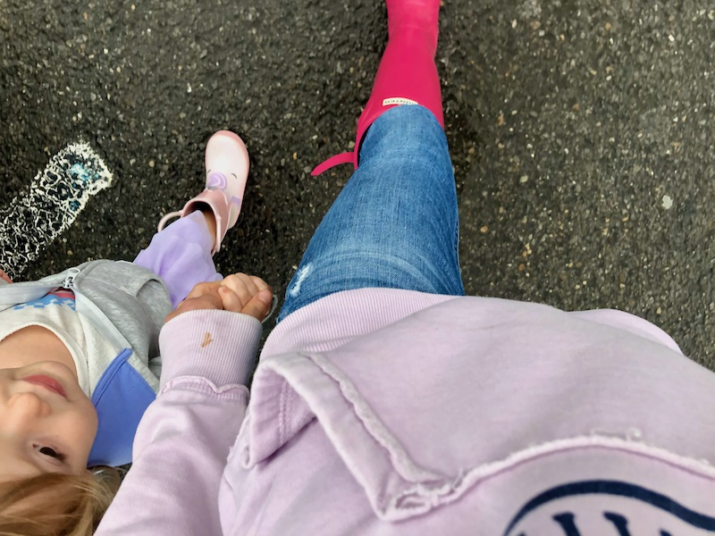 Mom and daughter wearing rain boots while walking