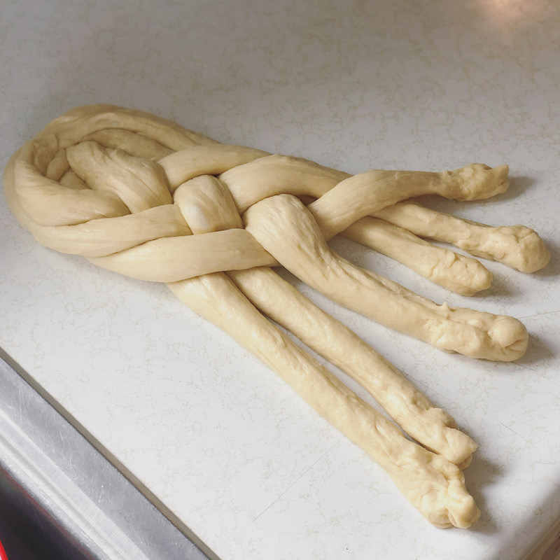 Six strand challah bread being braided