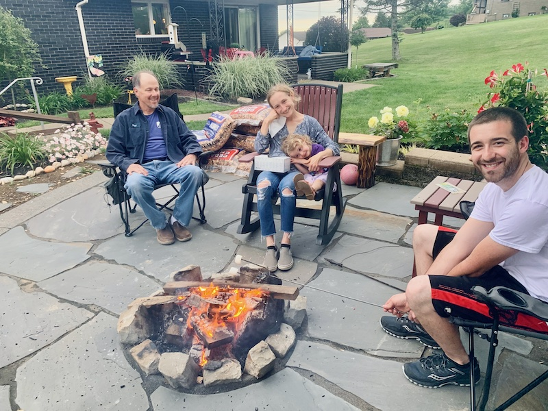 Family sitting by fire pit with s'mores