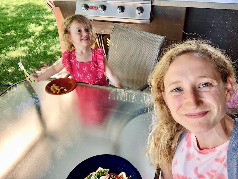 Mom and daughter eating lunch outside on glass table