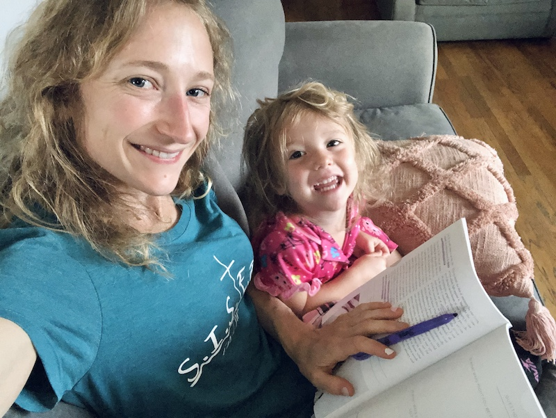 Mom and toddler daughter reading Bible study together on couch