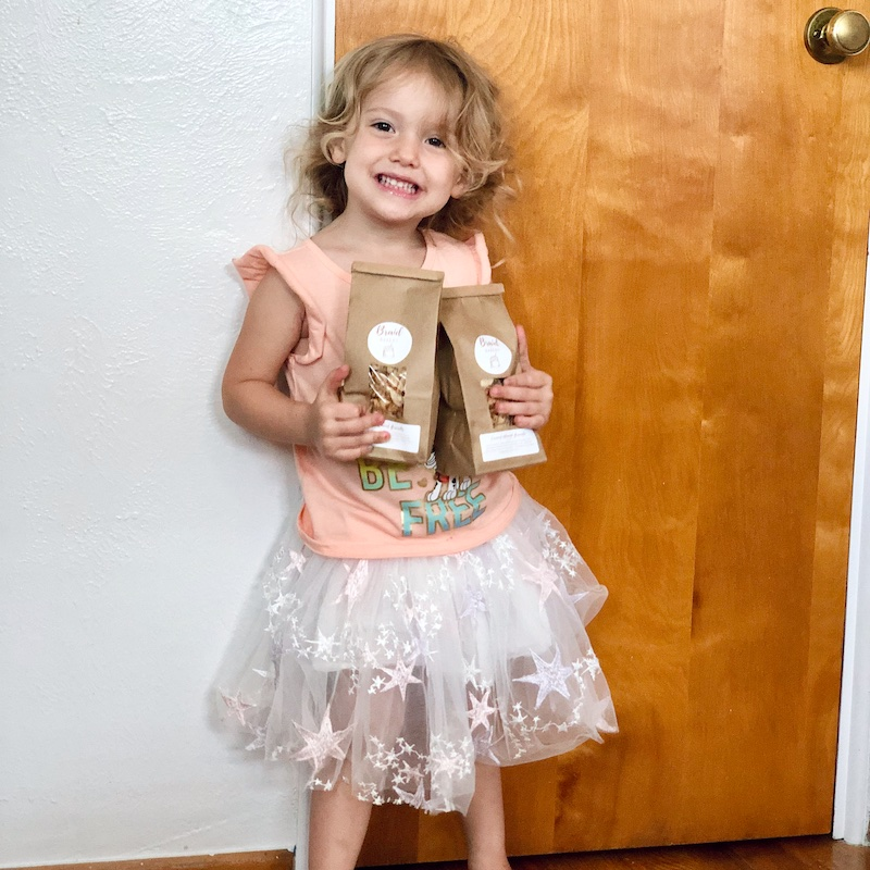Toddler holding bags of granola from Etsy shop.