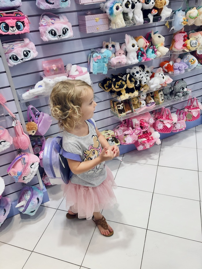 Little girl in Claire's with backpack on