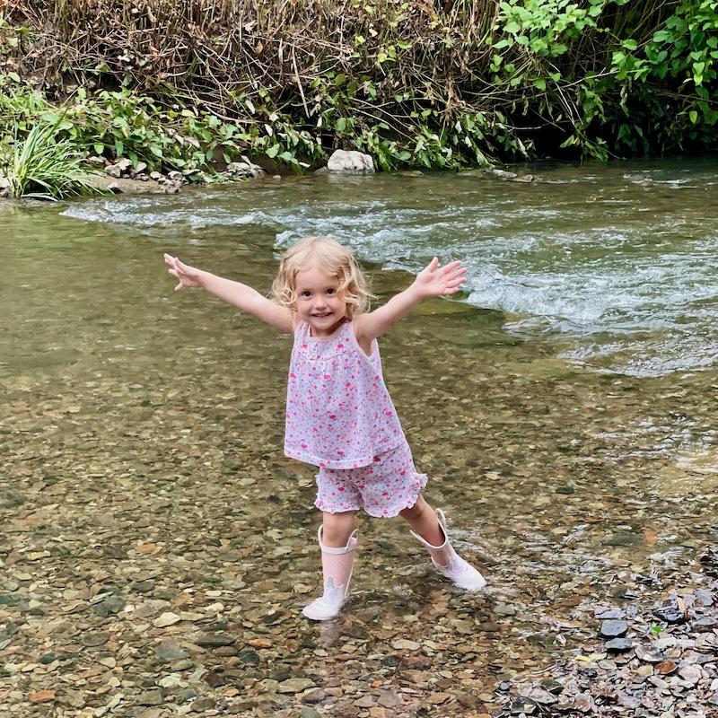 Toddler wearing rain boots in creek