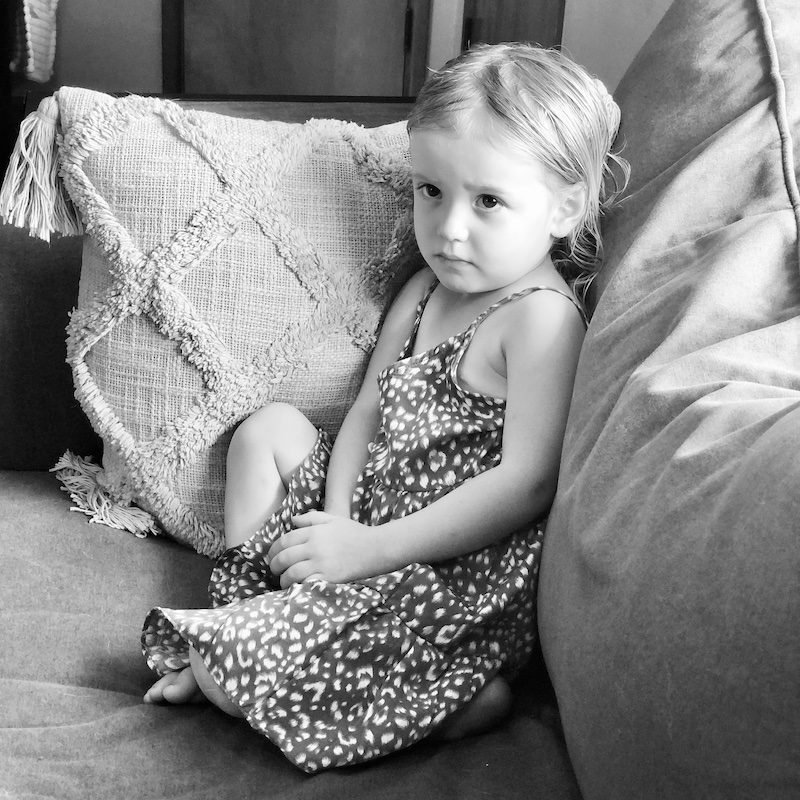 Black and white picture of toddler girl sitting on couch