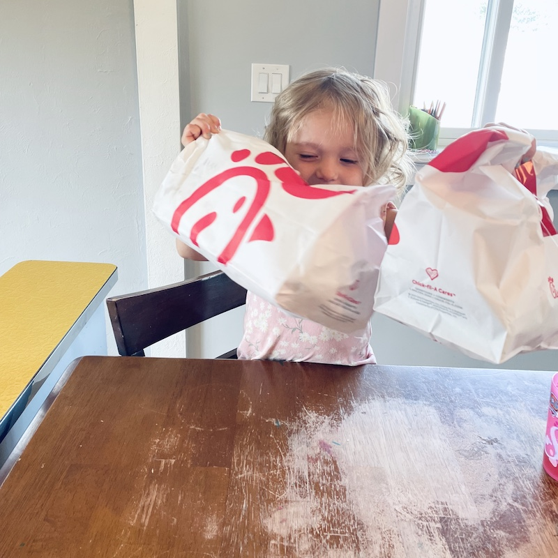 Toddler holding Chick-fil-A bags