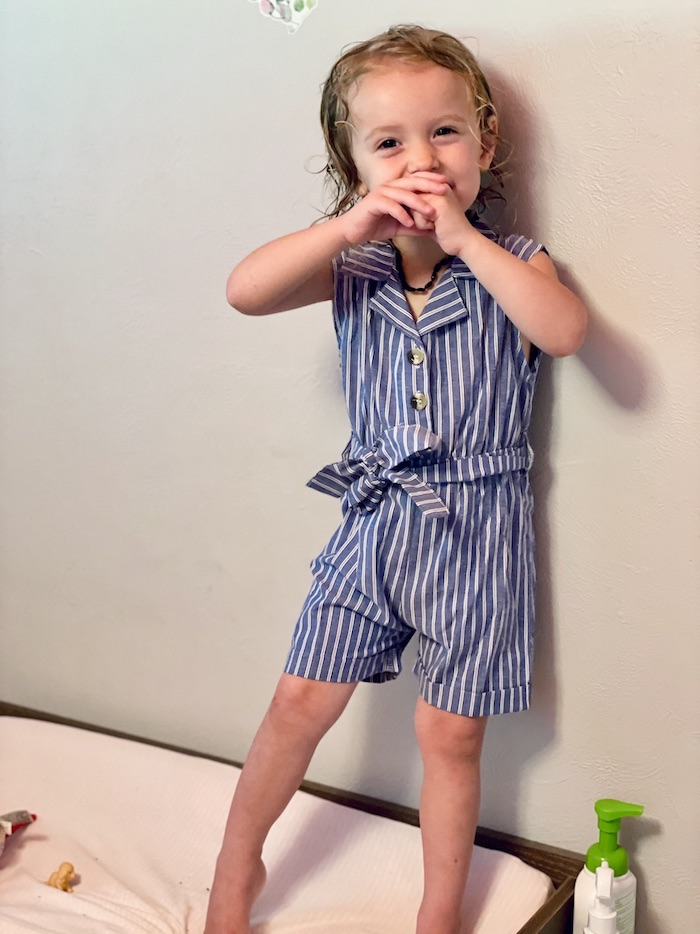 Toddler girl wearing blue and white striped romper
