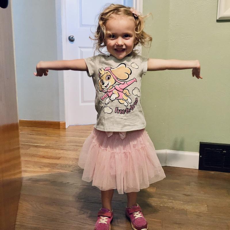 Toddler girl wearing skirt and Paw Patrol shirt