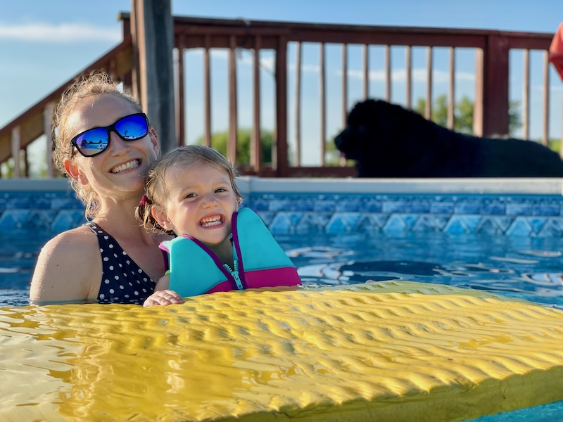 Mom and toddler swimming in pool
