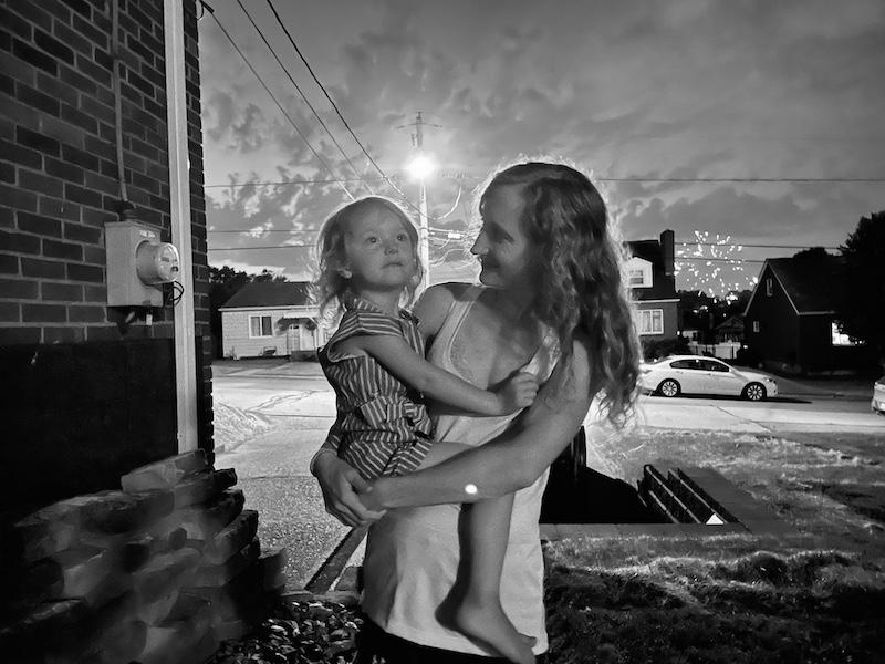 Mom holding toddler during fireworks black and white photo