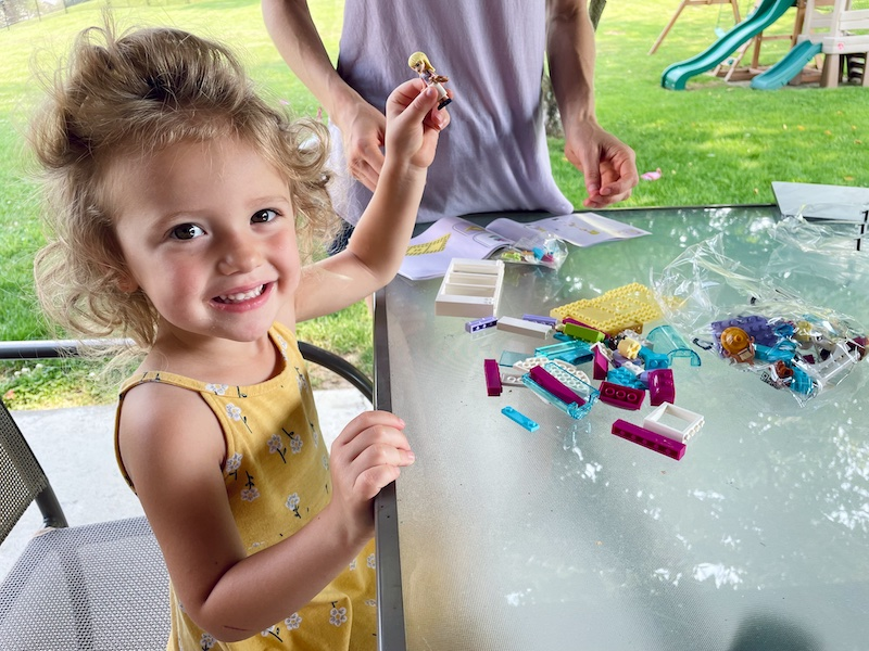 Toddler playing with LEGO Friends set outside