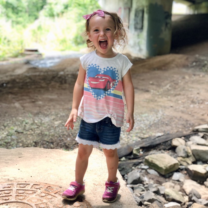 Toddler on path smiling with Cars shirt on