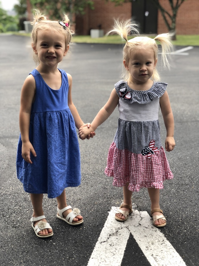 Toddler girls holding hands in Fourth of July dresses
