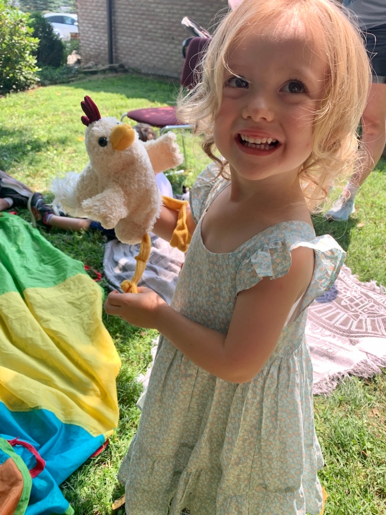 Toddler girl with chicken puppet