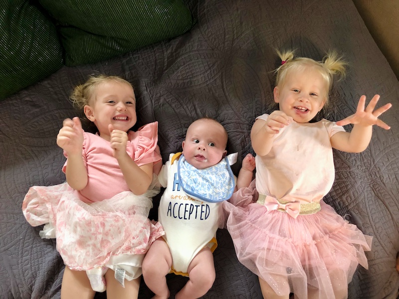 Toddler girls in matching tutu outfits and baby boy all laying together on bed
