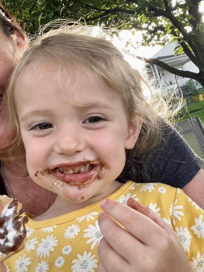 Toddler girl eating s'mores