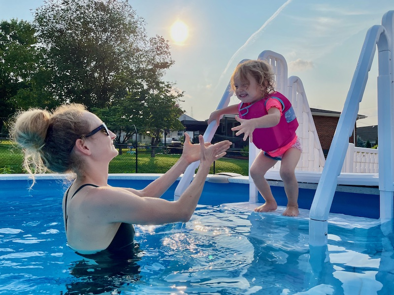 Toddler jumping off ladder and into pool.