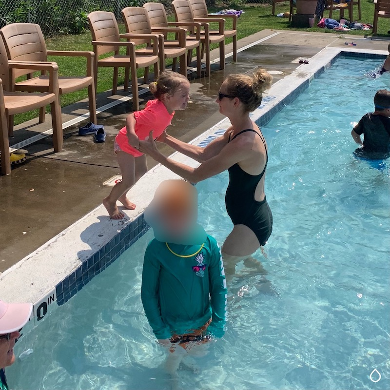 Mom catching toddler girl as she jumps in pool