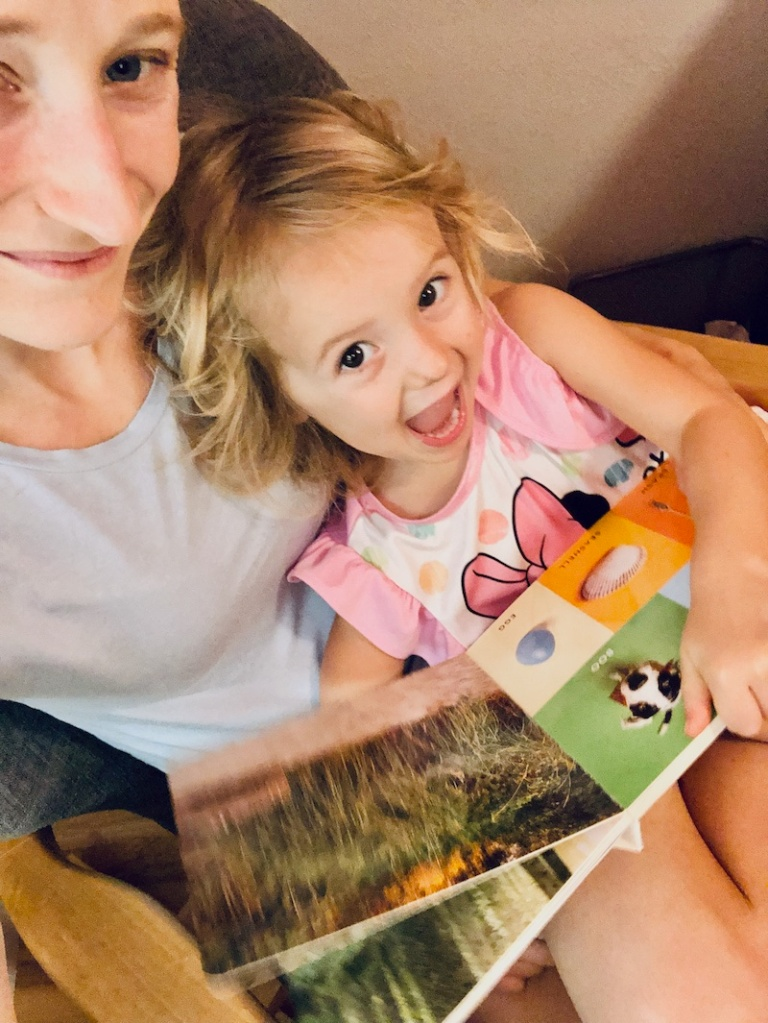 Mom and toddler reading book together