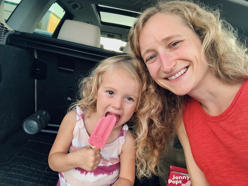 Mom and toddler eating Johnny Pops in the back of car