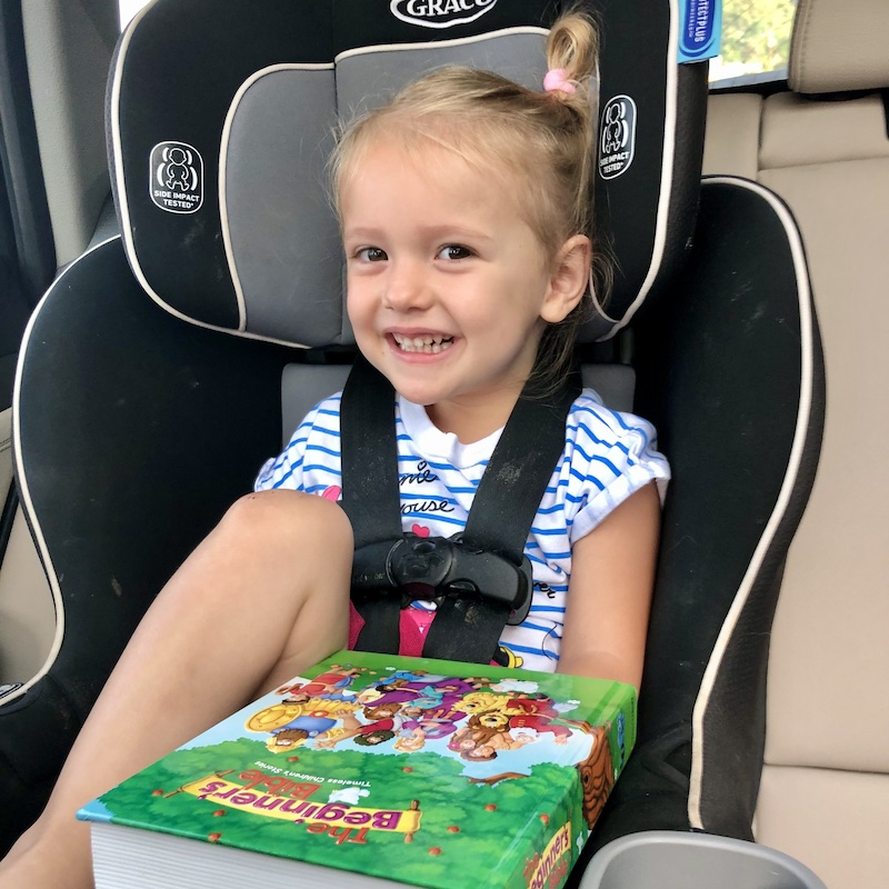 Toddler sitting in carseat with Bible